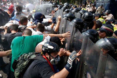 Anti-government protesters clash with the police during a protest in Caracas