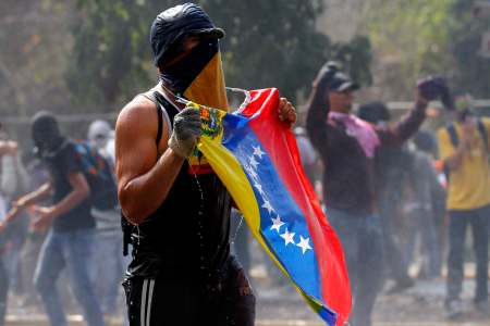 An anti-government protester is soaked by a water cannon during clashes with the police in Caracas